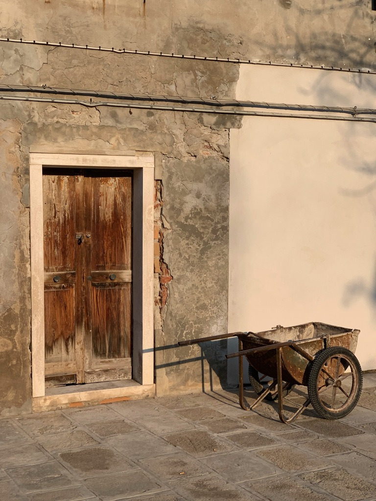 Closed wooden door and a wheelbarrow, Venice